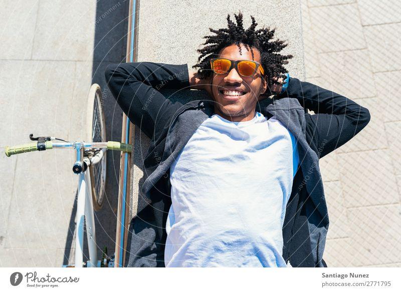 Ein gutaussehender Afro-Mann, der sich in der Nähe seines Fahrrads entspannt. Fixie Schickimicki Lifestyle laufen lügen Erholung genießend Fahrradfahren