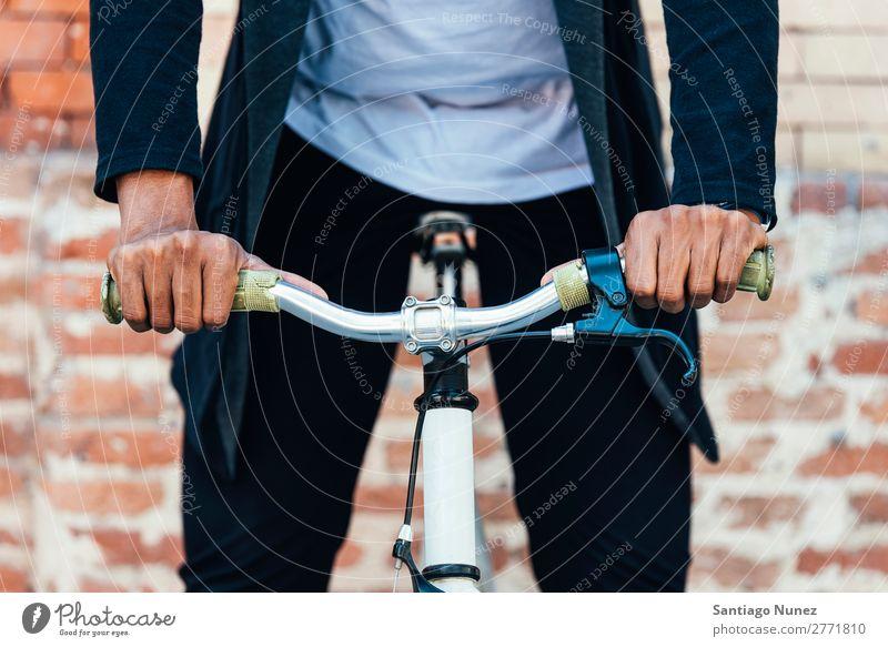 Gutaussehender Afro-Mann auf einem Fahrrad. Jugendliche Afro-Look schwarz Mulatte Afrikanisch Fahrradlenker Hand Fixie Schickimicki Lifestyle Fahrradfahren