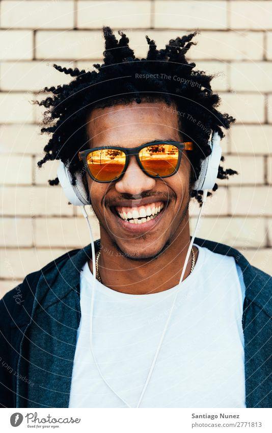 Porträt eines afro-ansehnlichen Mannes, der Musik hört. Jugendliche Afrikanisch schwarz Mulatte Afro-Look Kopfhörer Mobile hören Telefon Lifestyle stehen PDA