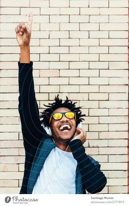 Porträt eines afro-ansehnlichen Mannes, der Musik hört. Jugendliche Afrikanisch schwarz Mulatte Afro-Look Kopfhörer zeigen Finger Mobile hören Telefon