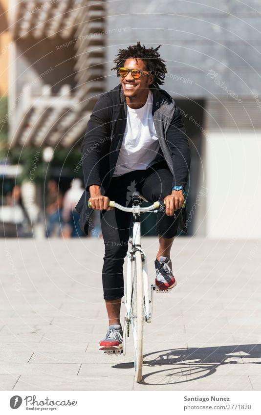 Gutaussehender Afro-Mann auf einem Fahrrad. Jugendliche Afro-Look schwarz Mulatte Afrikanisch Fixie Schickimicki Lifestyle Fahrradfahren Großstadt Stadt Mensch