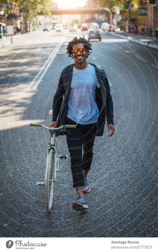 Ein gutaussehender Afro-Mann, der mit seinem Fahrrad unterwegs ist. Jugendliche Afro-Look schwarz Mulatte Afrikanisch Fixie Schickimicki Lifestyle Fahrradfahren