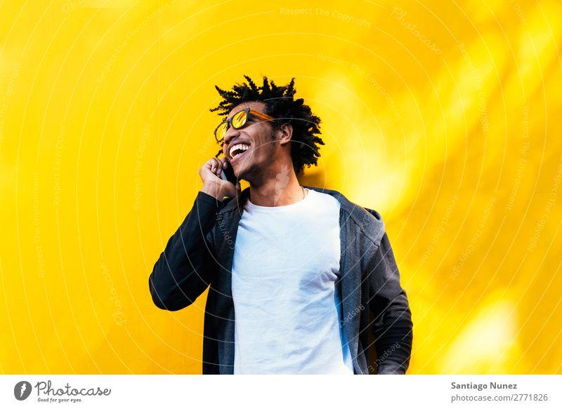 Porträt eines gutaussehenden Afro-Mannes mit seinem Handy. Jugendliche Afrikanisch schwarz Mulatte Afro-Look Mobile Telefon Lifestyle stehen benutzend