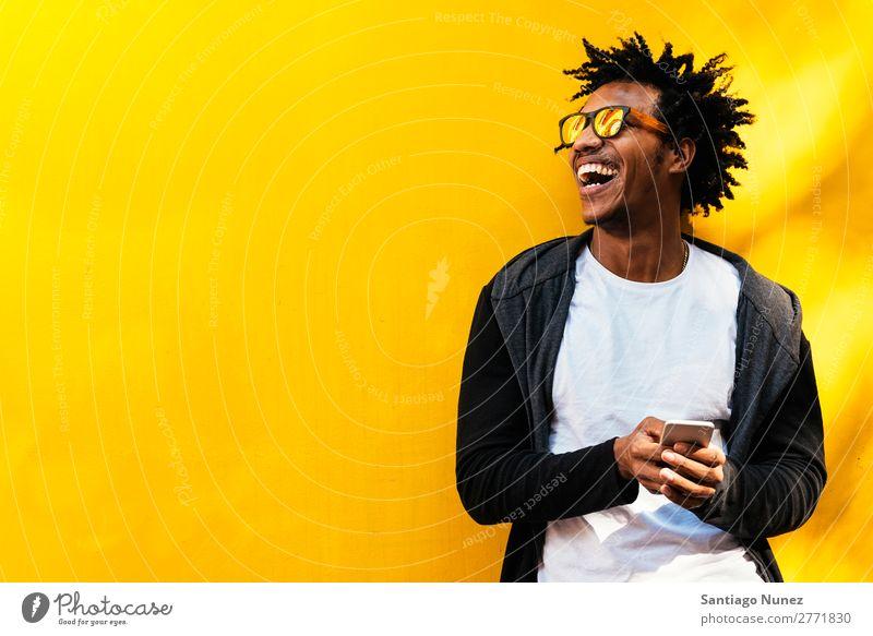 Porträt eines gutaussehenden Afro-Mannes mit seinem Handy. Mobile Glück Lächeln Afro-Look schwarz Afrikanisch Mulatte Telefon Schickimicki Lifestyle stehen