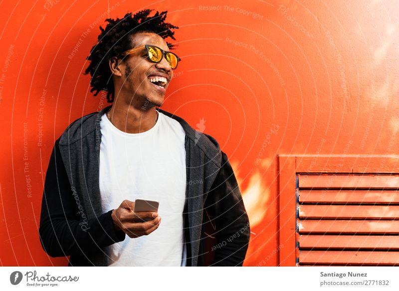 Afrojunger Mann benutzt Handy. Jugendliche Afrikanisch schwarz Mulatte Afro-Look Mobile Telefon Lifestyle stehen Fahrradfahren benutzend Solarzelle