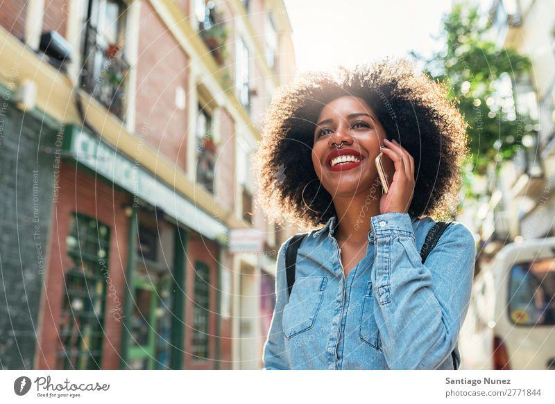 Schöne afroamerikanische Frau, die ein Handy auf der Straße benutzt. schwarz Afrikanisch Afro-Look Mensch Porträt PDA Jugendliche Mobile Telefon sprechen
