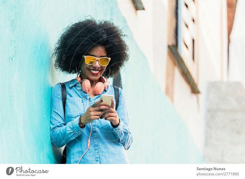 Schöne afroamerikanische Frau, die ein Handy auf der Straße benutzt. schwarz Afrikanisch Afro-Look Mensch Porträt PDA Jugendliche Mobile Telefon Chatten Texten