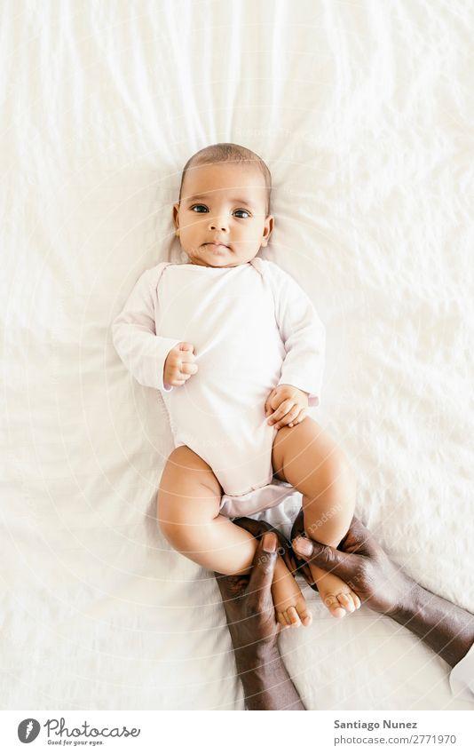 Süßes Babymädchen liegt in der Krippe. Junge Kind Kinderbett Mädchen lügen neugeboren Babybett multiethnisch Eltern Hand Afrikanisch vielfältig Mensch