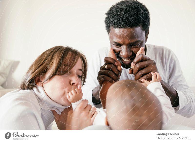 Glückliche Familie, Mutter, Vater und Baby. Junge Kind Bett Mädchen lügen neugeboren Eltern Familie & Verwandtschaft multiethnisch Afrikanisch vielfältig Mensch
