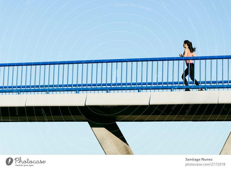 Junge Fitness-Läuferin, die auf der Stadtbrücke läuft. rennen Aktion Athlet sportlich Eisenbahn Frau Training üben Sport stark Körper anstrengen Mobile Telefon