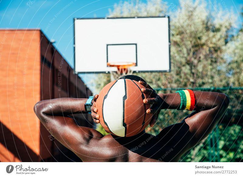 Männlicher Basketballspieler, der einen Ball hält. Aktion Afroamerikaner Rücken Rückansicht Korb schwarz Großstadt Stadtleben Gerichtsgebäude Tag üben Spielen