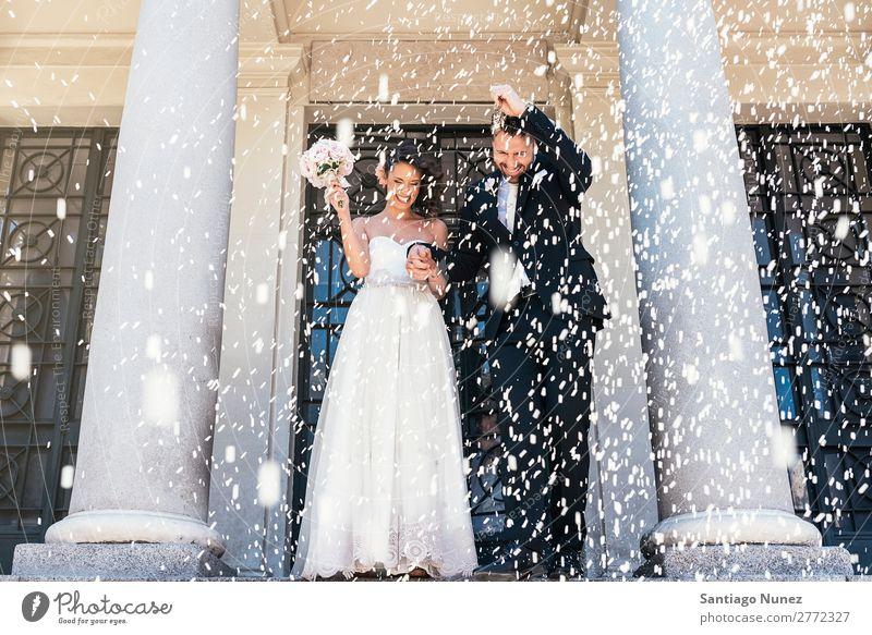 Neu verheiratetes Paar, das die Kirche verlässt. Hochzeit Reis Werfen Familie & Verwandtschaft Jungvermählter Glück Braut Mensch Frau weiß Mann Liebe