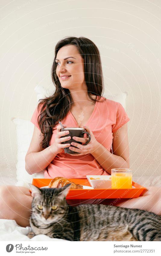 Glückliche Frau beim Frühstück in ihrem Schlafzimmer. Bett Kaffee Frucht Saft Orangensaft Croissant Ernährung Arbeit & Erwerbstätigkeit Technik & Technologie