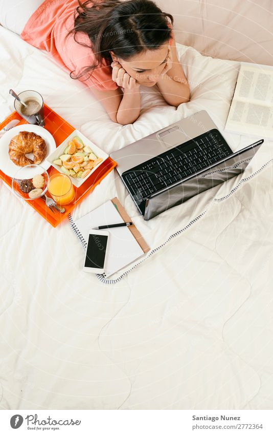 Frau, die den Laptop beobachtet und frühstückt. Frühstück Bett Notebook Kaffee Frucht Saft Orangensaft Croissant Ernährung Arbeit & Erwerbstätigkeit