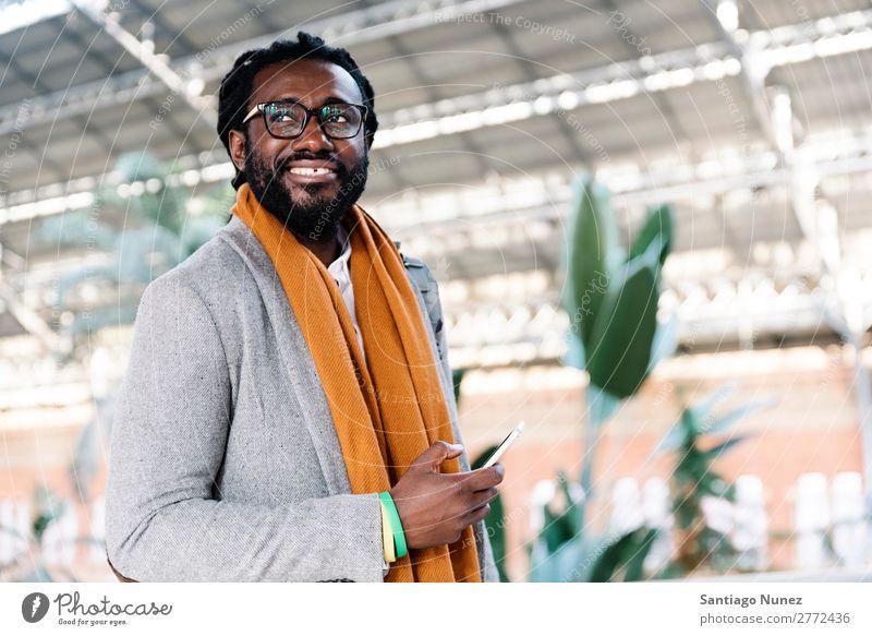 Geschäftsmann im Bahnhof. Mann schwarz Afrikanisch Amerikaner Business Handy Jugendliche Telefon Glück Mobile Innenaufnahme Straße PDA Büro Mensch