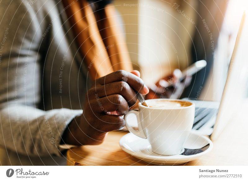 Geschäftsmann mit seinem Laptop im Coffee Shop. Mann schwarz Afrikanisch Amerikaner Business Handy Jugendliche Notebook Computer Café Kaffee Büro Mensch