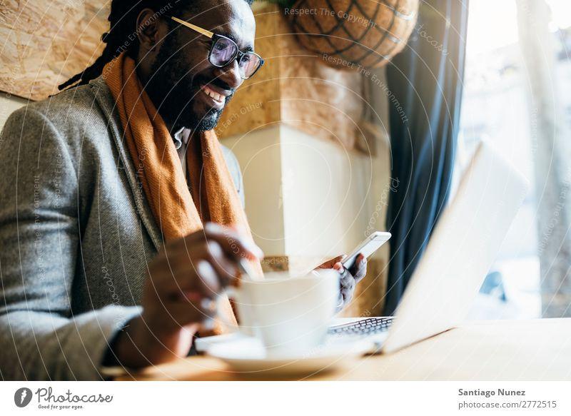 Geschäftsmann mit seinem Laptop im Coffee Shop. Mann schwarz Afrikanisch Amerikaner Business Handy Jugendliche Notebook Computer Coffee-Shop Kaffee Büro Mensch