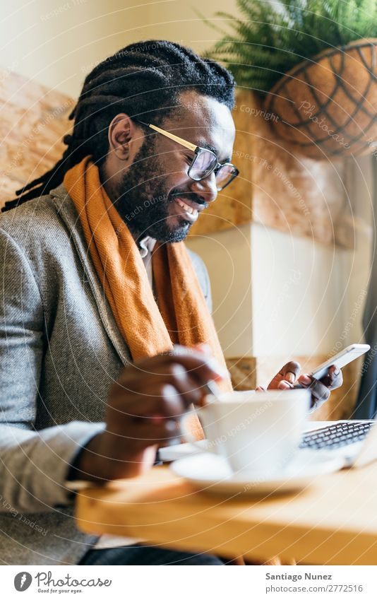 Geschäftsmann mit seinem Laptop im Coffee Shop. Mann schwarz Afrikanisch Amerikaner Business Handy Jugendliche Notebook Computer Glück Büro Mensch