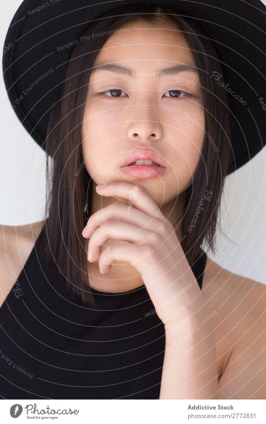 Junge asiatische Frau mit Posing im Studio mit Hut Stil modisch schön Mode Beautyfotografie Jugendliche Model Porträt attraktiv elegant Glamour hübsch Dame