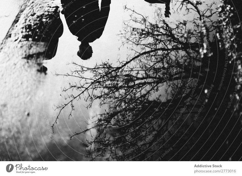 Menschen und Baum gespiegelt in einer Pfütze Entwurf Schwarzweißfoto Spiegel Silhouette Wasser laufen Asphalt Etage Beton Aktion Regen Stimmung Wetter