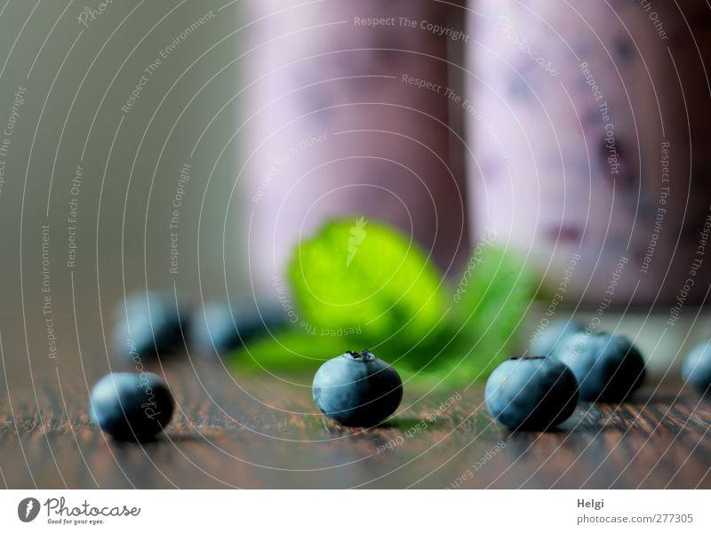 reife Heidelbeeren und grüne Blätter liegen auf einem Holztisch, im Hintergrund zwei Gläser mit Heidelbeersmoothie Lebensmittel Milcherzeugnisse Frucht