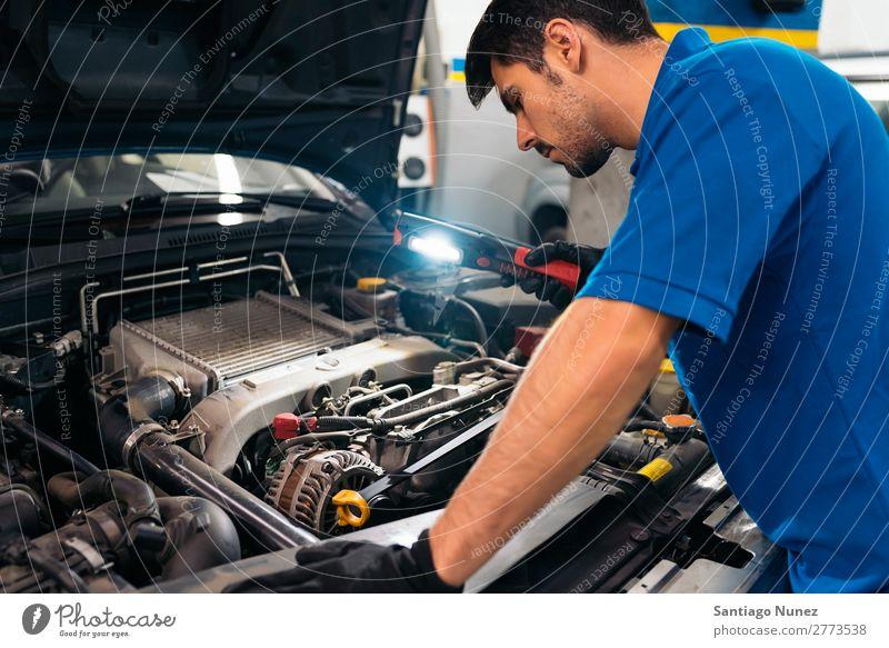 Professioneller Mechaniker Reparatur Auto. Erwachsene Mann Automechaniker blau Flugzeugwartung PKW Fahrzeug Werkzeug Licht Lampe Laterne Motor Lokomotive