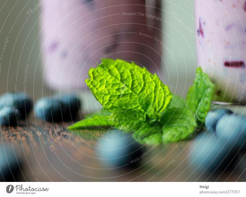 ein grünes Blatt von Minze liegt auf einem Tisch mit Blaubeeren und im Hintergrund zwei Gläser mit Blaubeersmothie Lebensmittel Milcherzeugnisse Frucht