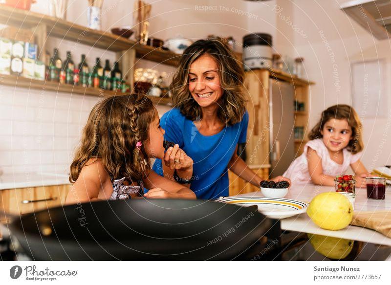 Kleine Schwestern kochen mit ihrer Mutter in der Küche. Kind Mädchen kochen & garen Verkostung Koch Schokolade Speiseeis Tochter Tag Glück Freude