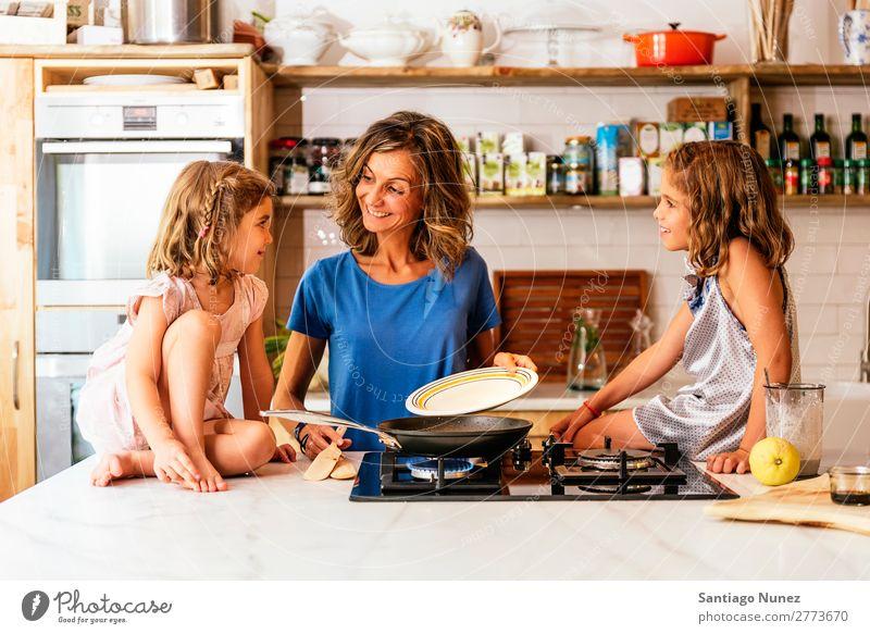 Kleine Schwestern kochen mit ihrer Mutter in der Küche. Kind Mädchen kochen & garen Koch Schokolade Speiseeis Tochter Tag Glück Freude Familie & Verwandtschaft