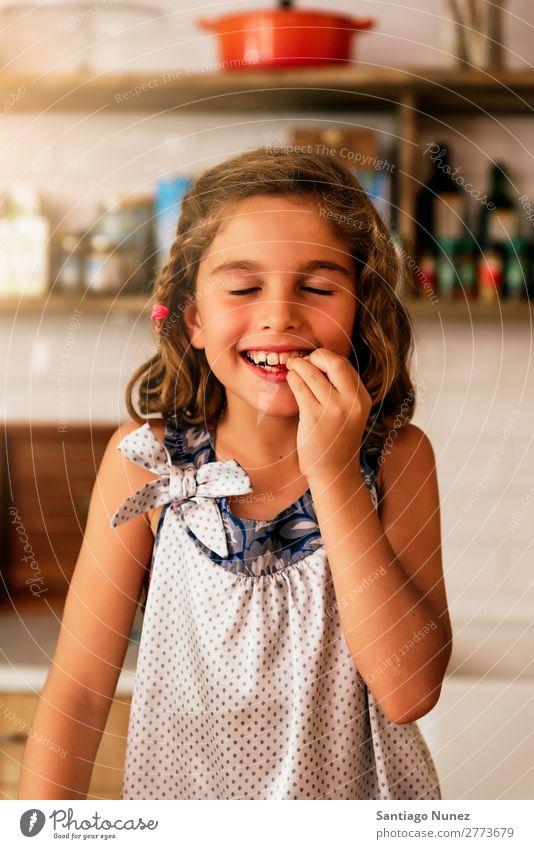 Kleines Mädchen isst Schokolade, während es Kekse backt. Kind Ernährung Fressen Verkostung Essen genießend Porträt Appetit & Hunger Lächeln lachen Mittagessen