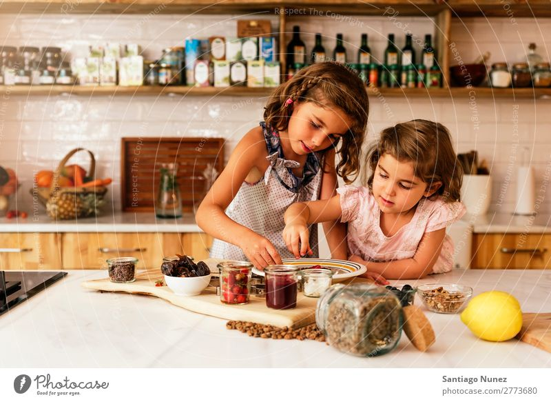 Kleine Schwestern Mädchen bereitet das Backen von Keksen vor. Kind kochen & garen Koch Küche Schokolade Speiseeis Erdbeeren Tochter Tag Glück Freude