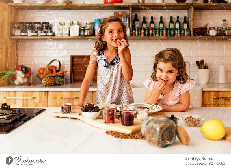 Kleine Schwestern Mädchen bereitet das Backen von Keksen vor. Kind kochen & garen Koch Küche Schokolade Essen Verkostung Erdbeeren Tochter Tag Glück Freude