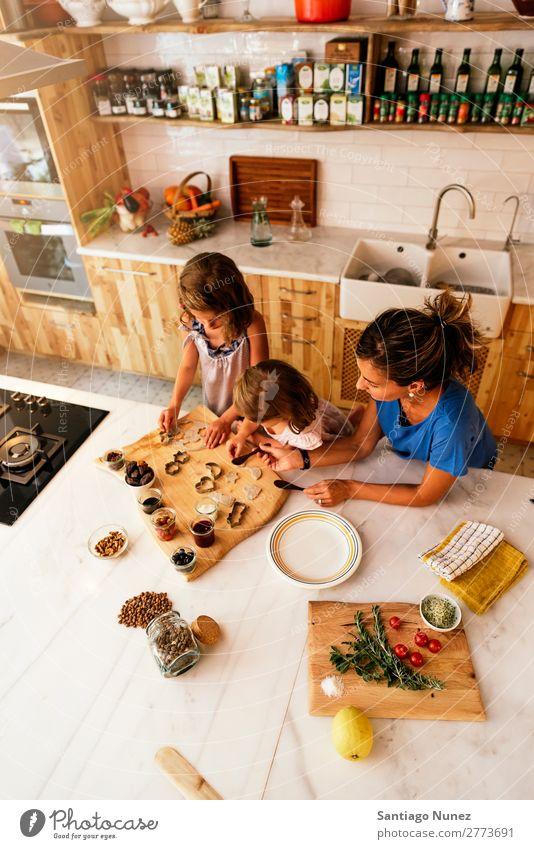 Kleine Schwestern kochen mit ihrer Mutter in der Küche. Kind Mädchen kochen & garen Koch Schokolade Marmelade Erdbeeren Tochter Aufstrich Tag Glück Freude