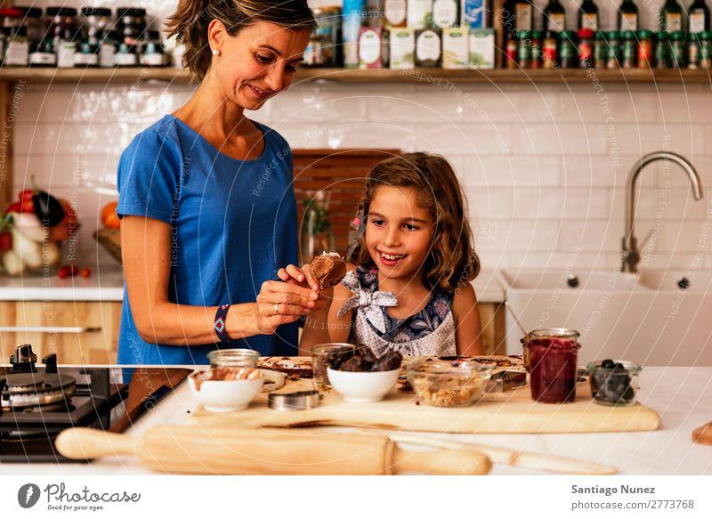 Kleines Mädchen kocht mit ihrer Mutter in der Küche. kochen & garen Koch Schokolade Speiseeis Tochter Tag Glück Freude Familie & Verwandtschaft Liebe backen