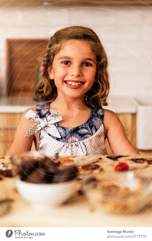 Porträt eines kleinen Mädchens beim Backen von Keksen. Kind Ernährung Fressen Verkostung Essen genießend Appetit & Hunger Lächeln lachen Mittagessen Baby