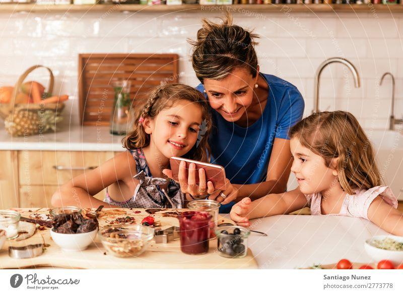 Kleine Schwestern kochen mit ihrer Mutter in der Küche. Kind Mädchen kochen & garen Koch Schokolade Mobile PDA benutzend App Solarzelle Rezept Tochter Tag Glück