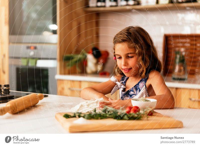 Porträt eines kleinen Mädchens beim Backen von Keksen. Kind Ernährung kochen & garen Koch Küche Bäckerei backen Appetit & Hunger Vorbereitung machen Lächeln