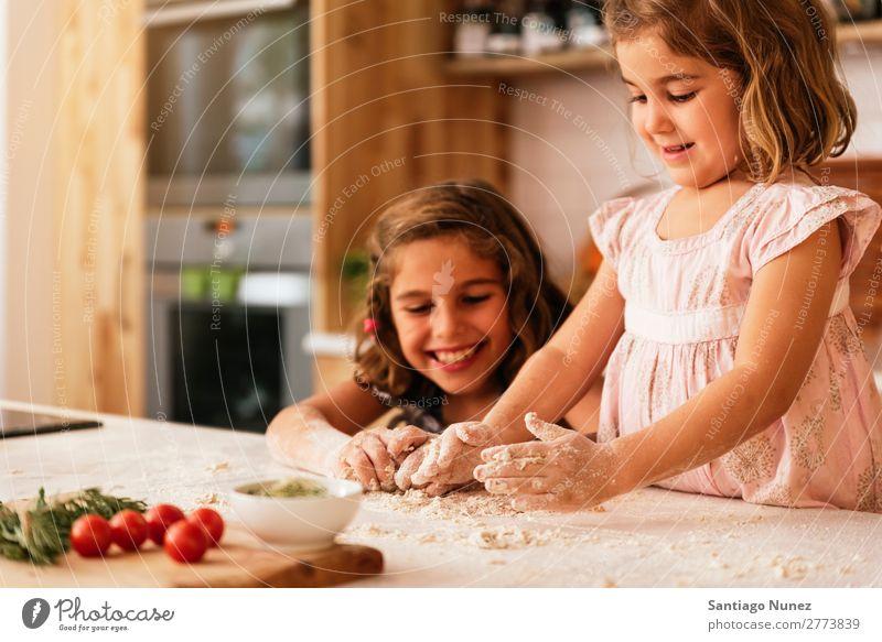 Kleine Schwestern kneten Teig und bereiten sich auf das Backen von Keksen vor. Kind Mädchen kochen & garen Koch Küche Mehl Hand Teigwaren dreckig gefärbt lachen