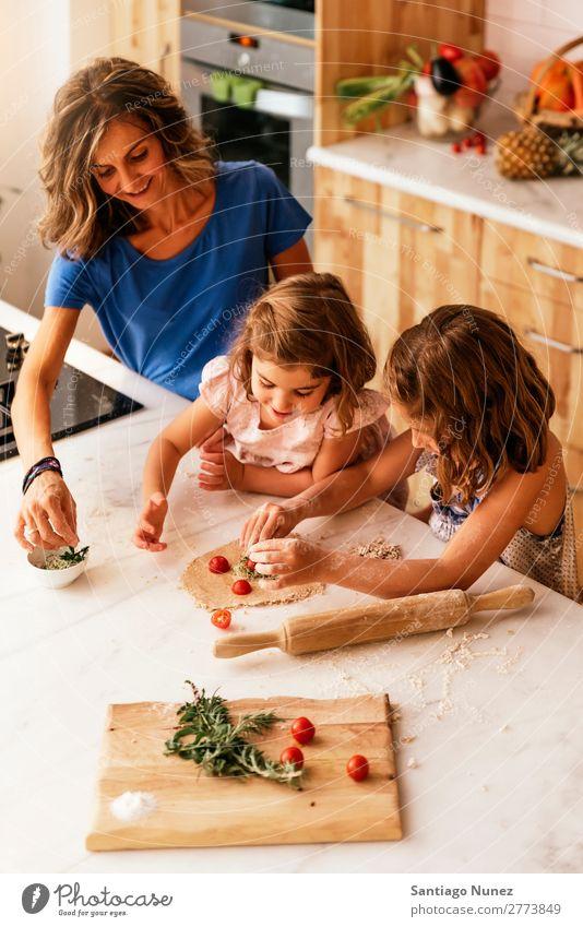 Kleine Schwestern kochen mit ihrer Mutter in der Küche. Kind Mädchen kochen & garen Koch Tomate Pizza Gemüse Tochter Aufstrich Tag Glück Freude