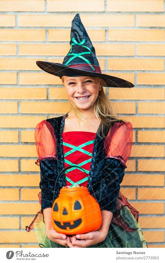 Porträt eines schönen Mädchens, das sich als Hexe auf der Straße verkleidet hat. Halloween Kind malen Freude Familie & Verwandtschaft Schwester Kürbis Angst