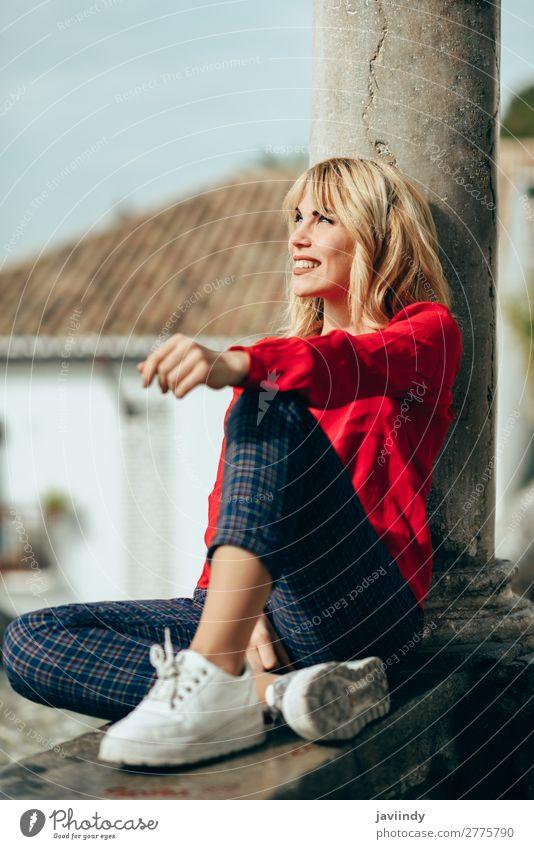 Glückliche Frau, die auf einem urbanen Hintergrund sitzt und sich sonnt. Lifestyle Stil schön Haare & Frisuren Mensch feminin Junge Frau Jugendliche Erwachsene
