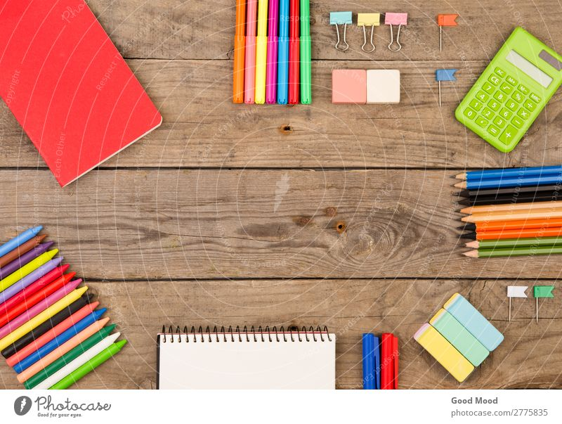 Buch, Taschenrechner, Notizblock, Buntstifte und andere Schreibwaren Tisch Kind Schule Studium Büro Kindheit Accessoire Holz hell grün rot Hintergrund Kulisse