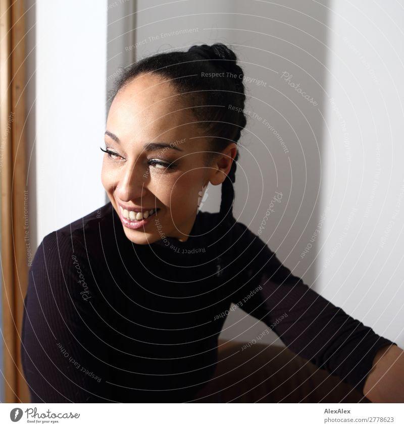 Portrait einer Frau mit Zopf Freude schön Zufriedenheit Junge Frau Jugendliche 18-30 Jahre Erwachsene 30-45 Jahre T-Shirt schwarzhaarig Locken Lächeln sitzen