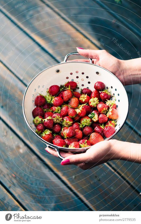 Weibliche Hand hält eine Schale mit frischen Erdbeeren. Frucht Vegetarische Ernährung Schalen & Schüsseln Sommer Tisch Frau Erwachsene Natur Holz lecker