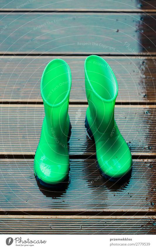 Regenstiefel, die auf einer Holzterrasse stehen, während es regnet. Freude Sommer Kind Mensch Frau Erwachsene Mann Wetter Mantel Schuhe Stiefel Gummistiefel