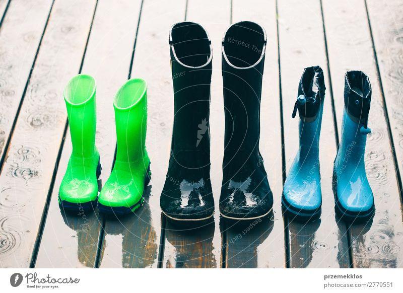 Reihe von Gummistiefeln, die auf einer Holzterrasse stehen, während es regnet. Freude Sommer Kind Mensch Frau Erwachsene Mann Wetter Regen Mantel Schuhe Stiefel