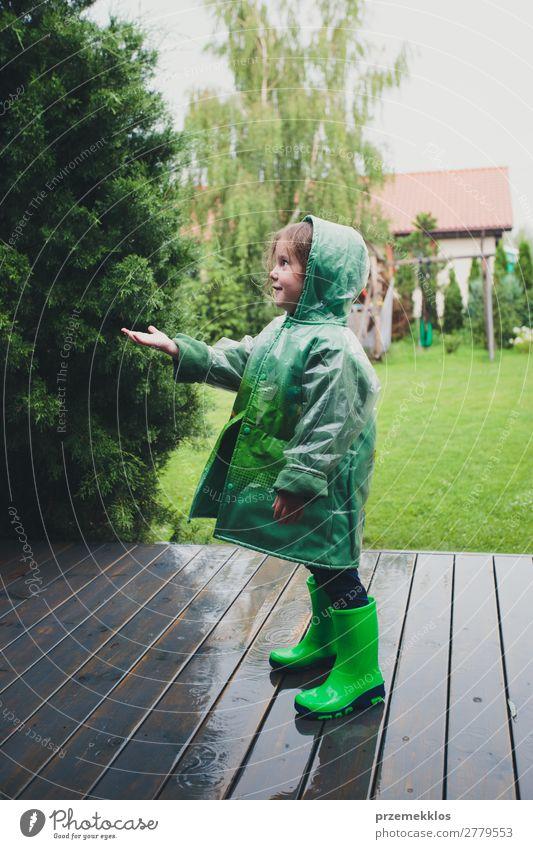 Kleines Mädchen, das im Regen steht und einen grünen Regenmantel trägt. Lifestyle Freude Glück Sommer Kind Mensch Frau Erwachsene Kindheit Wetter Mantel Stiefel