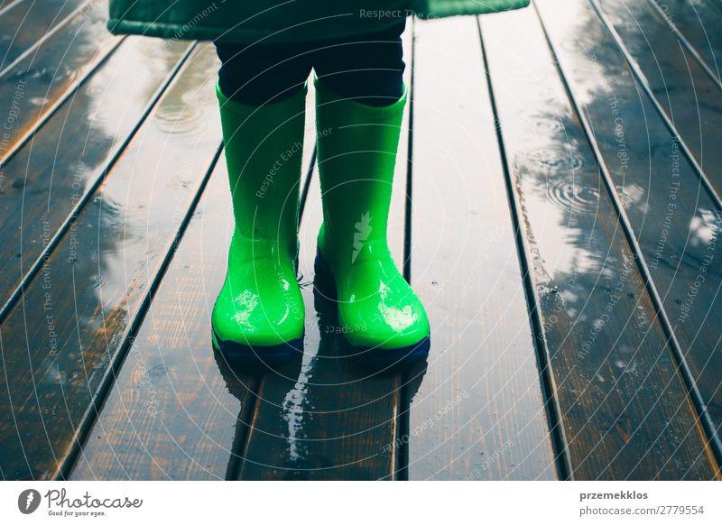 Kind steht auf einer Veranda und trägt grüne Gummistiefel und Regenmantel. Freude Sommer Mensch Junge Wetter Mantel Schuhe Stiefel klein nass niedlich kariert