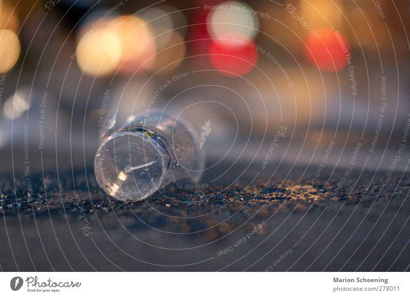 Wasserbecher auf der Straße Becher Farbfoto Außenaufnahme Nacht Starke Tiefenschärfe Plastikbecher kaputt leer achtlos Textfreiraum rechts Kunststoffmüll