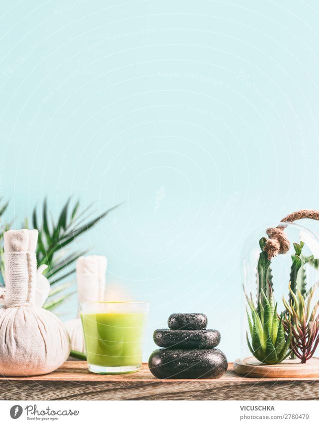 Spa-Hintergrund mit Massagegeräten: Stapel von Massagesteinen, Aromatherapiekerzen, Kräuterstempel auf Holztisch mit Sukkulentenpflanzen auf hellblauem Hintergrund. Wellness-Behandlung